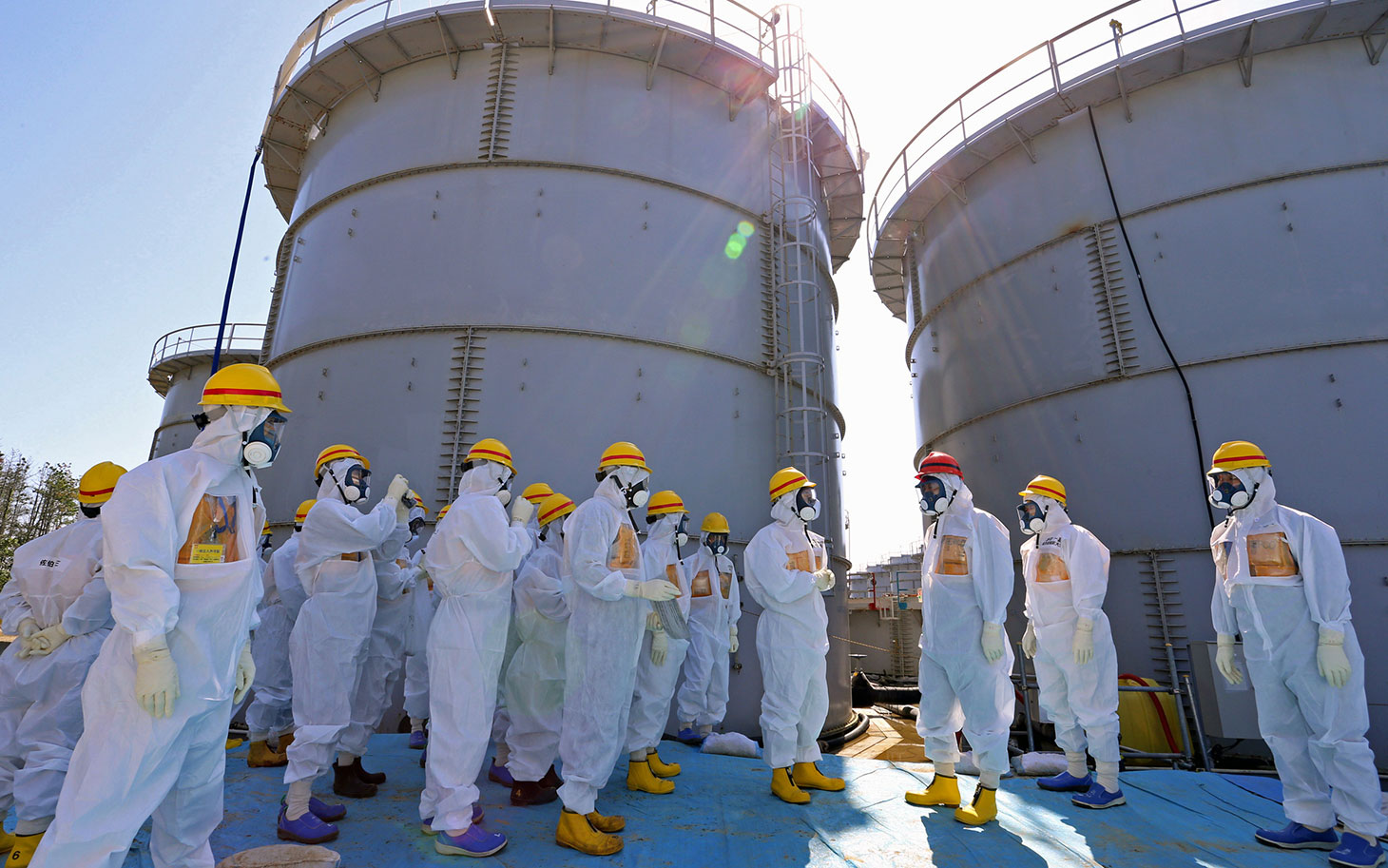 Japanese Prime Minister Shinzo Abe was briefed on the situation at the Fukushima Dai-ichi nuclear power plant as he toured the facility back on Sept. 19, 2013.  chief Akira Ono (4th L) in front of two tanks (back) which are being dismantled after leaking contaminated water, during his tour to the tsunami-crippled plant in Okuma, Fukushima Prefecture, northeastern Japan on September 19, 2013. Abe told Fukushima's operator to fix radioactive water leaks as he toured the crippled nuclear plant on September 19, less than two weeks after assuring the world the situation was under control. AFP PHOTO / Japan Pool  JAPAN OUT        (Photo credit should read JAPAN POOL/AFP/Getty Images)